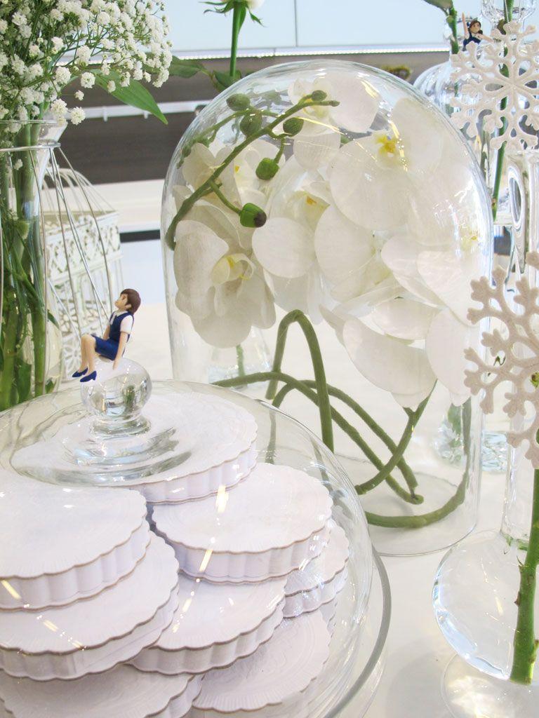 """A única flor artificial usada nessa decoração da vitrine da Ornare da Gabriel Monteiro da Silva, feita por Carol e Fernanda Lovisaro, foi essa orquídea dentro da cúpula (da Zara Home). """"A cúpula dá um efeito muito bonito na decoração da mesa, mas se você usar flor natural, ela tende a liberar água e deixar o vidro embaçado"""", conta Carol."""