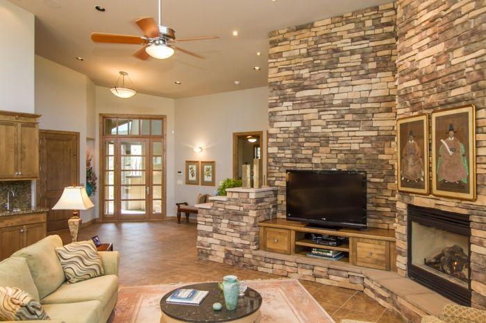 ein kompaktes Wohnzimmer mit Kamin, Fernseher auf einem Regal ...