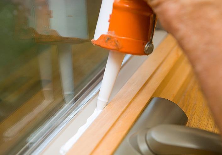 Applying caulk to a window frame to prevent air leakage. This caulk ...