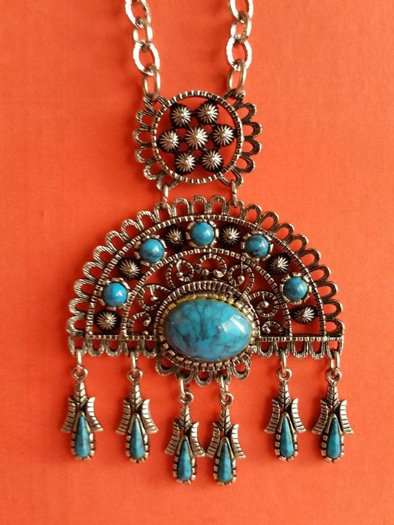 This fantastic vintage necklace from the 1970s is perfect for summer! This Native American-style necklace features sweet little corn cob pendants dangling down from a sturdy, well-made silver-tone pendant with faux turquoise details.