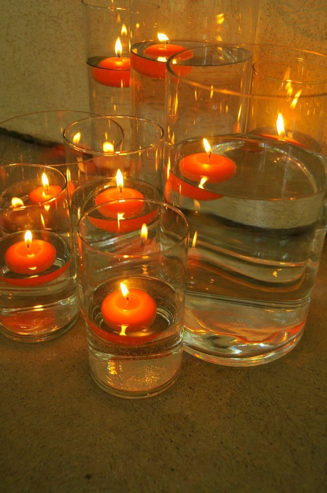 Cylinders With Water And An Orange Floating Candle