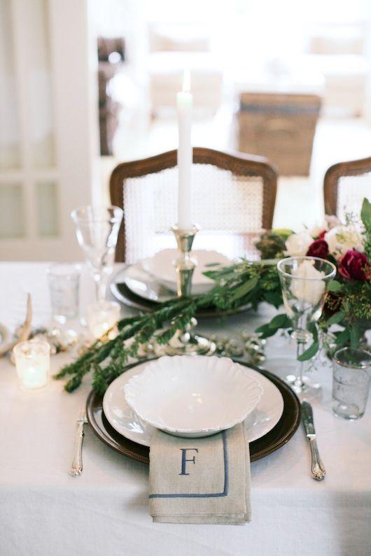 Beautiful seasonal greenery top the place settings at this table!