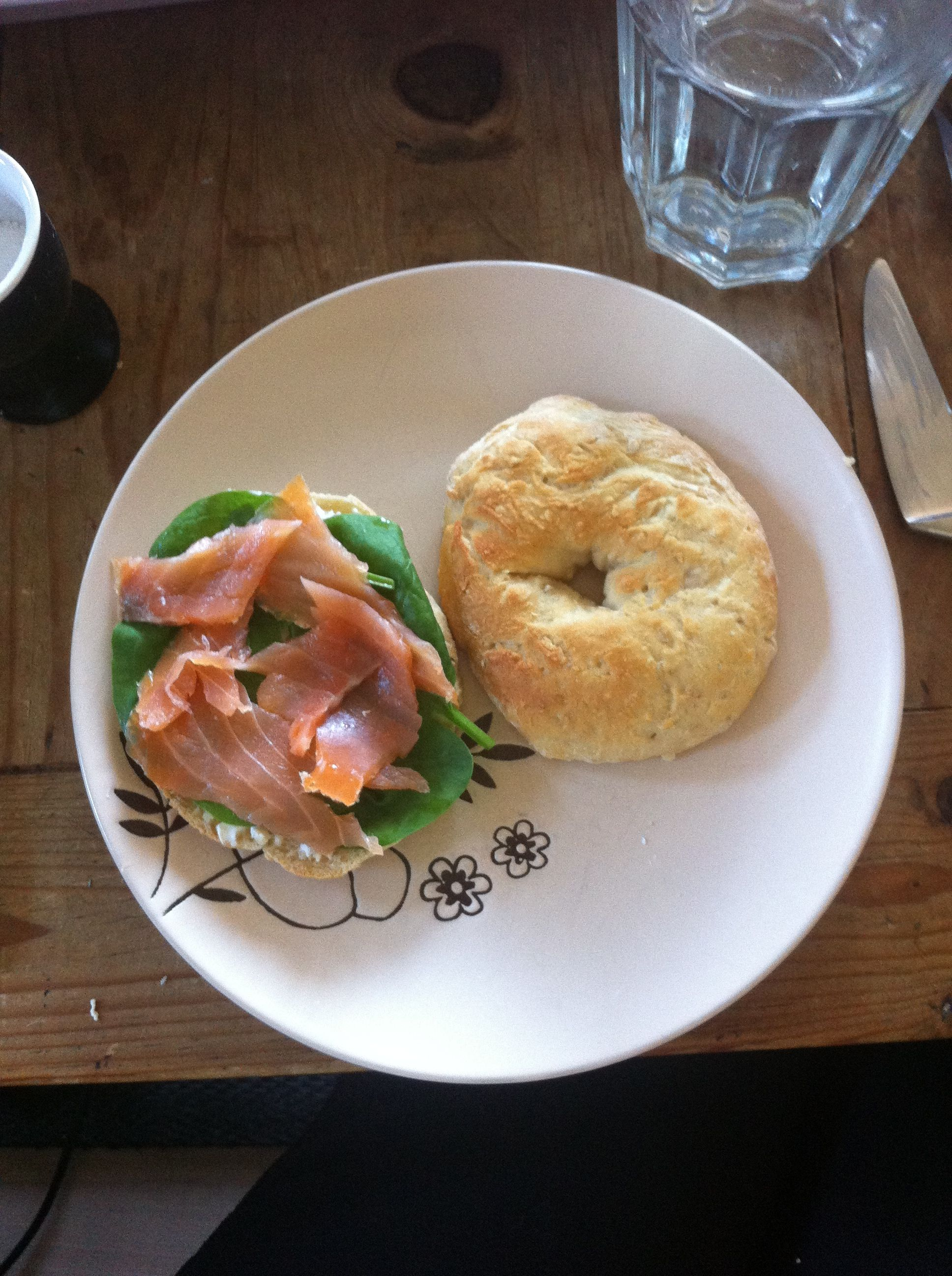 Homemade wholegrain bagel with lox and spinach.
