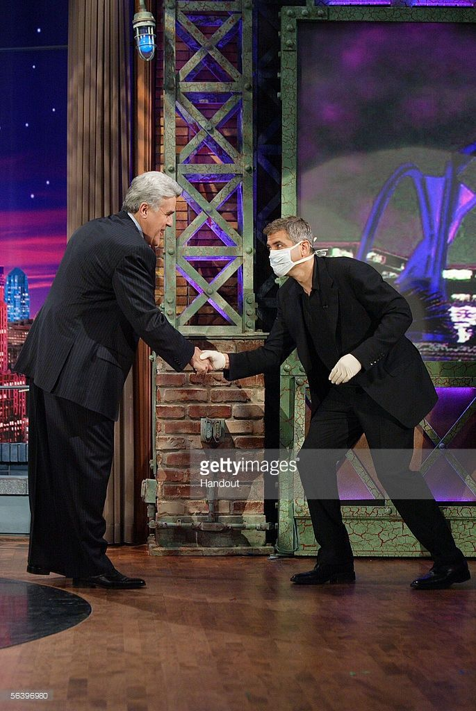 Actor George Clooney walks onstage wearing a surgical mask and gloves after finding out that host Jay Leno of the 'Tonight Show' was fighting a cold December 8, 2005 in Burbank, California.