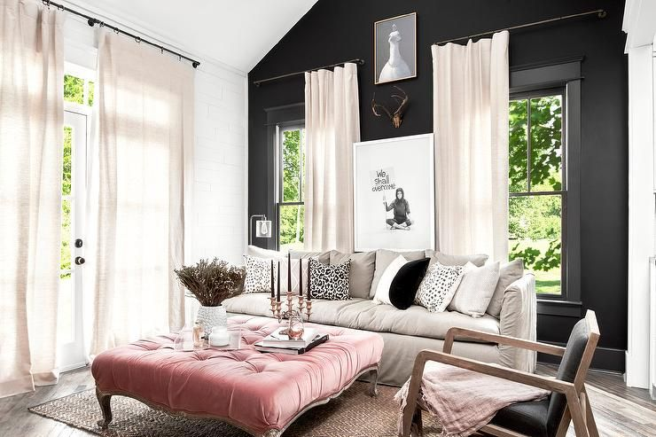 Chic living room features a black accent wall lined with a gray slipcovered sofa lined black and white pillows facing a French pink tufted velvet ottoman as coffee table placed atop a jute chevron rug.