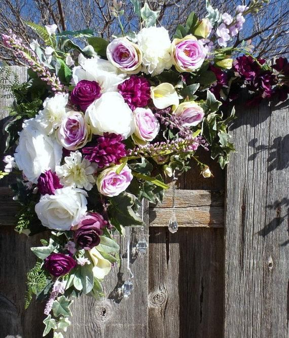Wedding Arbor Flowers  Arch Corner Swags  Plum, Lavender and whiteWedding decorations is part of Wedding decor Arch - Rose Arbor Corner Swags in shades of Plum, Lavender and White with just a touch of Pink  It starts off with an assortment of greenery including Lambs Ear, Dusty Miller and Ivy  On top of the lush greens are an assortment of Roses in shades of White, Lavender and Plum  It has several other flowers as well including Delphinium in both plum and lavender, Peonies, Ranunculus, and Mums  The arch flowers come in 2 pieces to go in the corners of your arch Each piece has 3 crystals hanging from it to dress it up  The flowers are High Quality realistic silk  This swag makes a stunning addition to your wedding decorations     This swag can be made with your wedding colors just convo me with any changes that you may need   Your swag will come wrapped in tissue and bubble wrap packaged in a sturdy box to ensure a safe arrival   The swag measures approximately 50   FG  WD WAS3PC1716