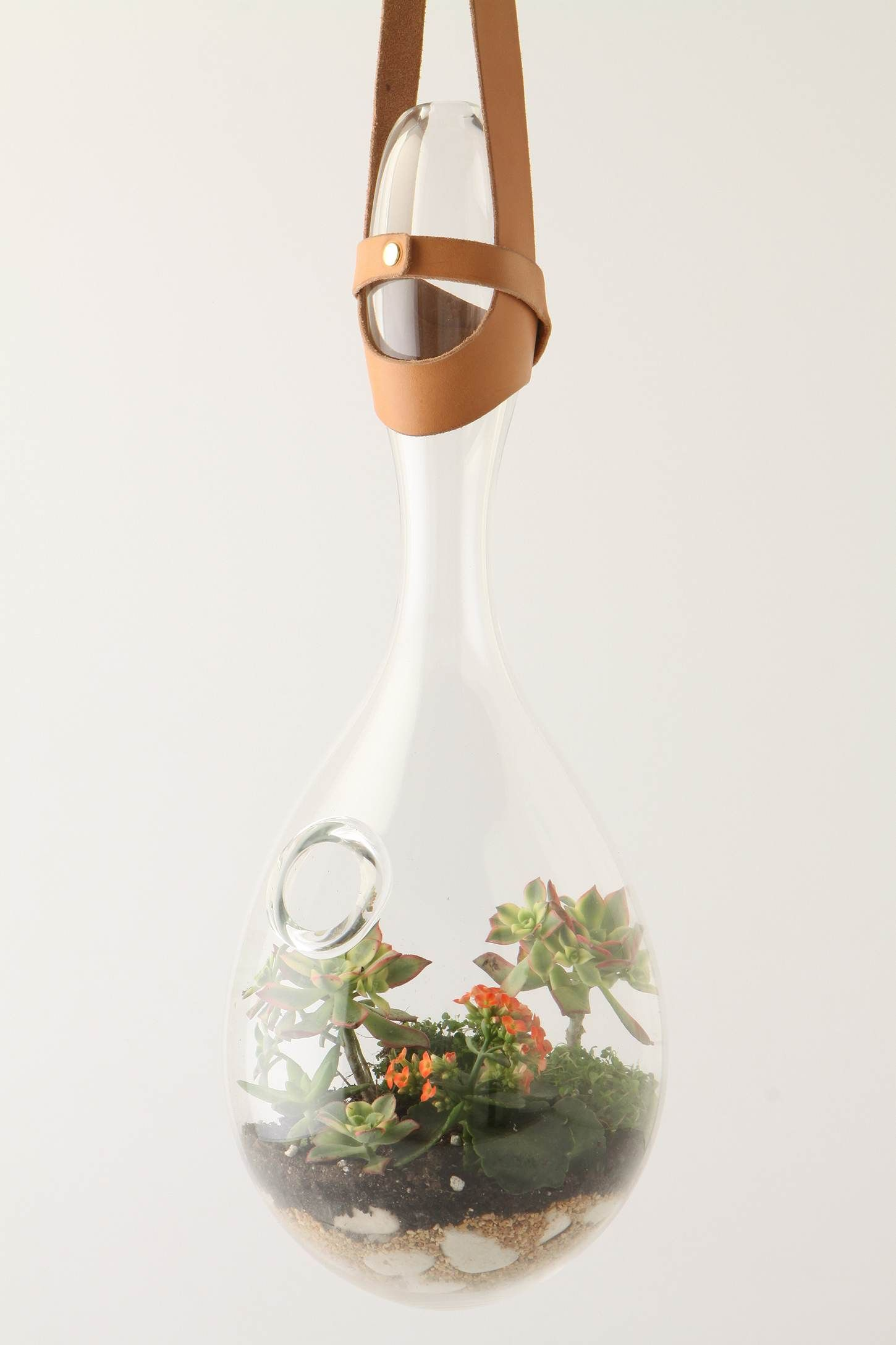 Dangling From A Neutral Leather Sling An Amorphous Glass Vessel
