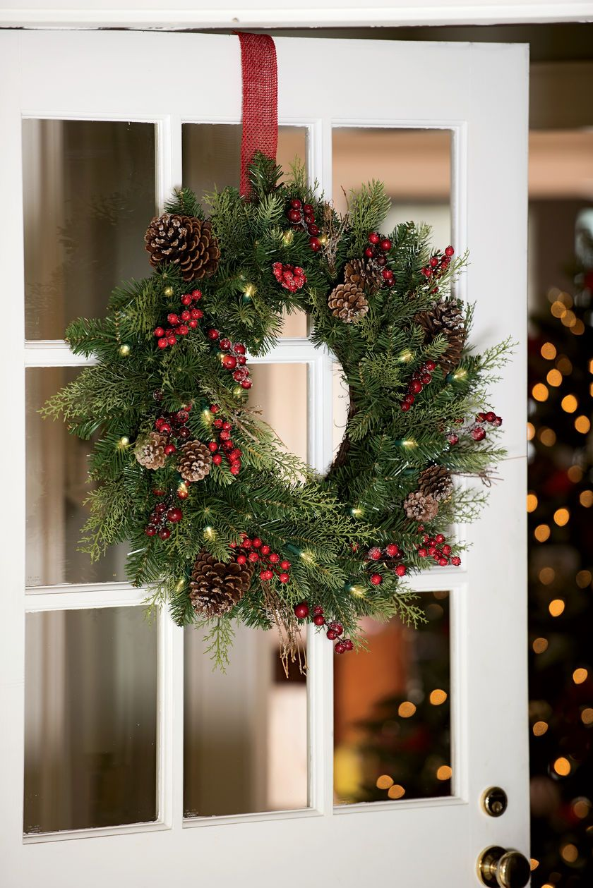 realistic faux pine and balsam greenery real pinecones faux berries and warm white led lights give this outdoor christmas wreath its woodsy charm
