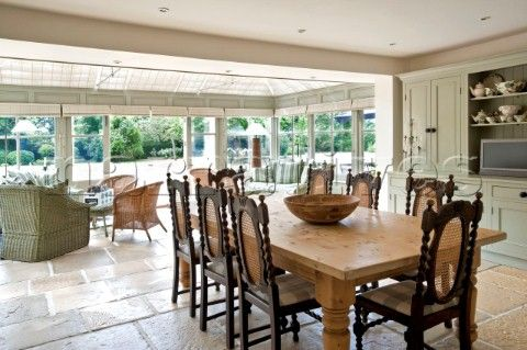 Wooden dining table and chairs in open plan flagstone kitchen ...