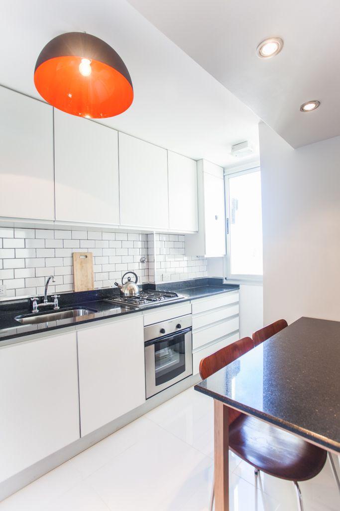 Cocina de muebles blancos, mesadas y mesa de granito negro