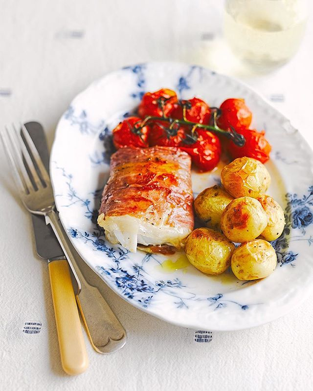 Quick and easy one for dinner tonight. baked pollock...par boil your spuds 5mins, Season the fish with sea salt and black pepper, then wrap in ham. Place in a baking dish with the tomatoes & potatoes. Season again and drizzle with oil. Bake in the oven for 12 to 18 minutes, depending on the thickness of the fillets. Check the fish with a skewer and cook for another minute or so if it's not done. Serve! Hit the direct link in my bio for the recipe online. Big love JO xxx