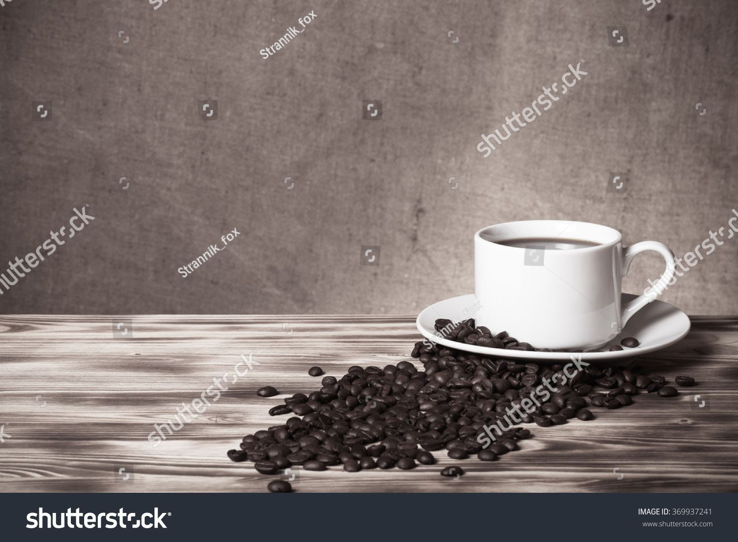 Coffee beans and coffee in white cup on wooden table