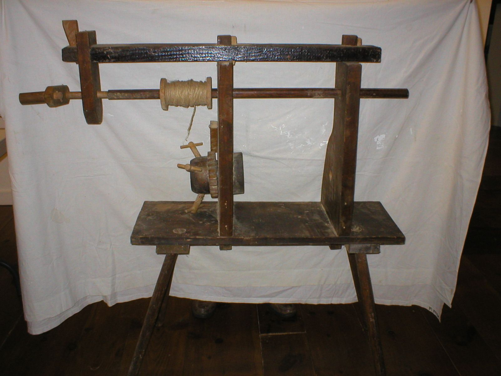 This is a mid-20 century broom making machine. It is operated by placing the shaft through two holes, with the brush part of the broom oriented to the left (in photo). The rushes were bound using the crank and spool of twine. At Chatham Historical Society, Chatham, MA. #atwoodhouse, #chathamhistoricalsociety, #chatham, #capecod, #broom, #maker, #machine, #tool
