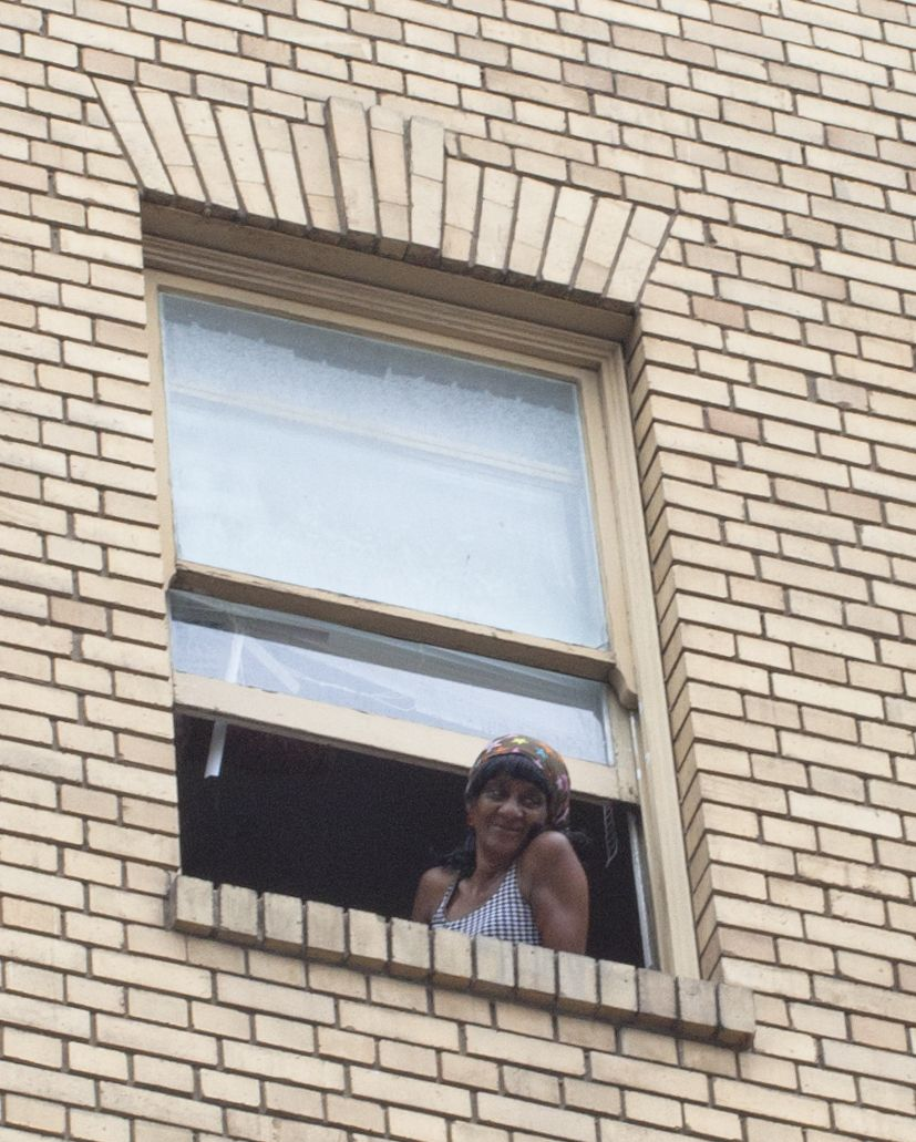 Woman Staring Out Of An Upper Story Window Off Mission