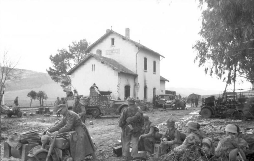 1943, Tunisie, Sidi Nsia, Des soldats allemands devant la gare. On peut voir un Half-track Personnel Carrier M3 US de prise