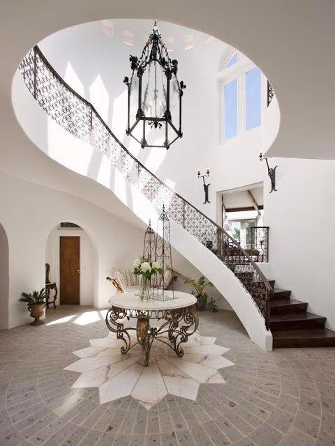 Grand foyer design, twisted staircase with a soft neutral tone with added Morrocan influence