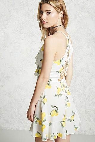 A woven cami dress featuring an allover lemon print, a surplice flounce neckline, tiered crossover hem skirt, a lace-up back, and a concealed back zipper.