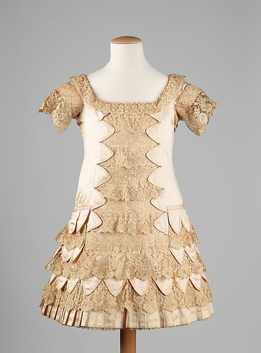 1879 Girl's Dress  Culture: American  Medium: silk, linen  Documented as being worn by Mina at just six and a half years of age, this is a very beautiful party dress. Made with fine machine-made lace, a great deal of workmanship went into creating this piece for a special occasion. Seen on the dress are the same decorative forms that were popular in 1870s women's garments. The original color was a very vibrant pink, but as with many silk garments of the nineteenth century, it has begun to…