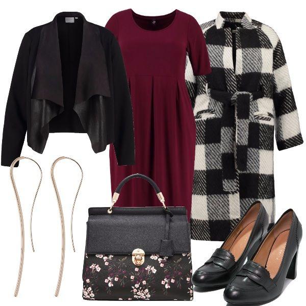 Blazer in finta pelle, vestito in maglina color gelso e cappotto wrap. Come accessori la borsa a mano doppio effetto, le décolleté nere, e gli orecchini rigidi.