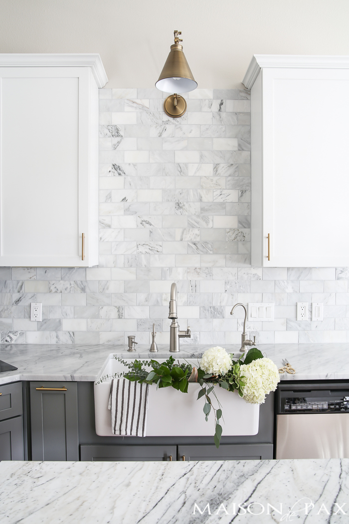 Gray and White and Marble Kitchen Reveal - White marble kitchen, Kitchen tiles design, White kitchen tiles, Trendy farmhouse kitchen, Kitchen marble, Replacing kitchen countertops - Gray and white cabinets, marble subway tile, Carrara countertops, a farmhouse sink, and brass hardware give this marble kitchen a classic yet modern look