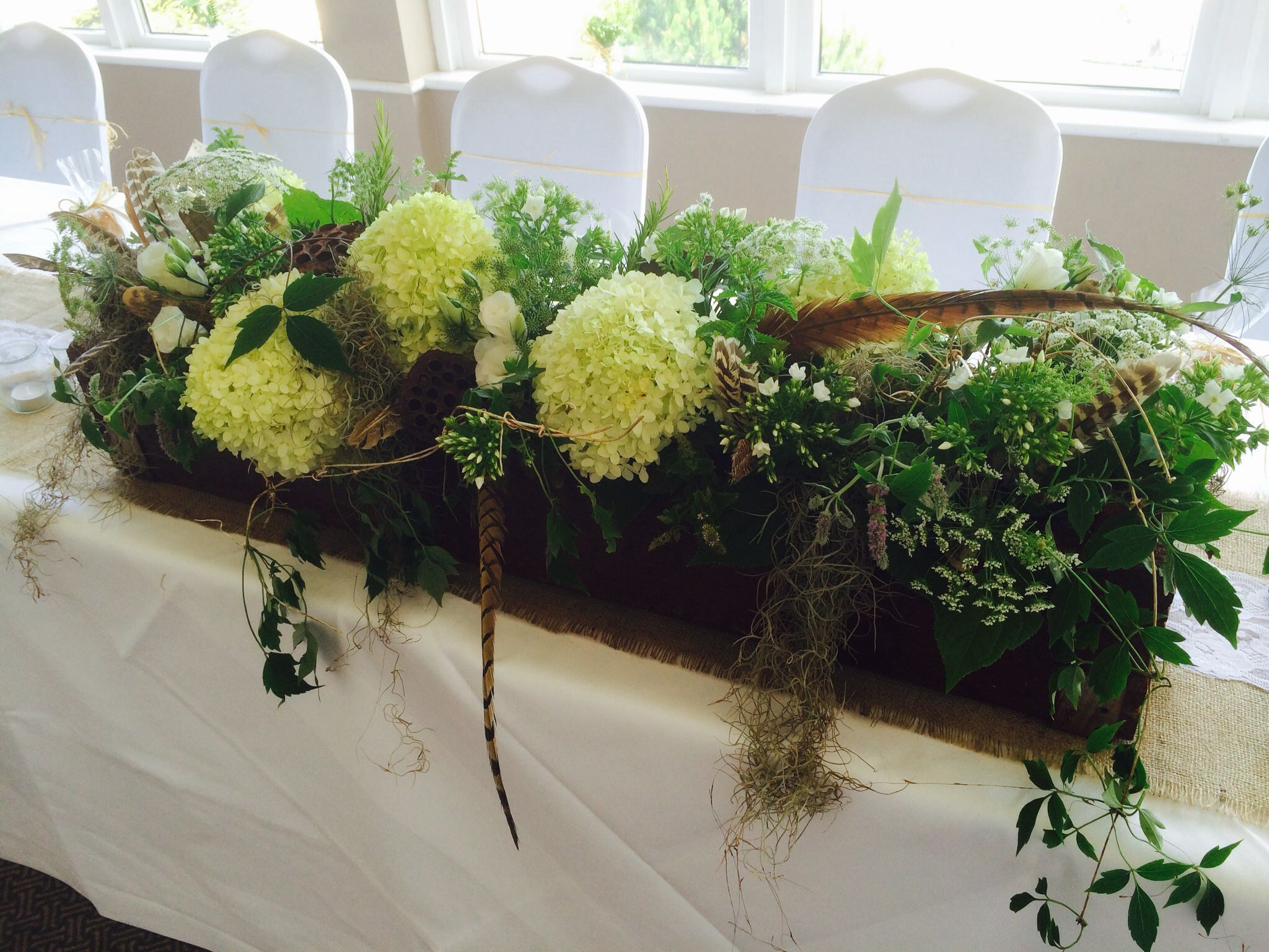 Wooden trough decorated with fresh herbs, hydrangeas, feathers, moss, mint, rosemary, lotus pods, www.weddingflowersincornwall.co.uk