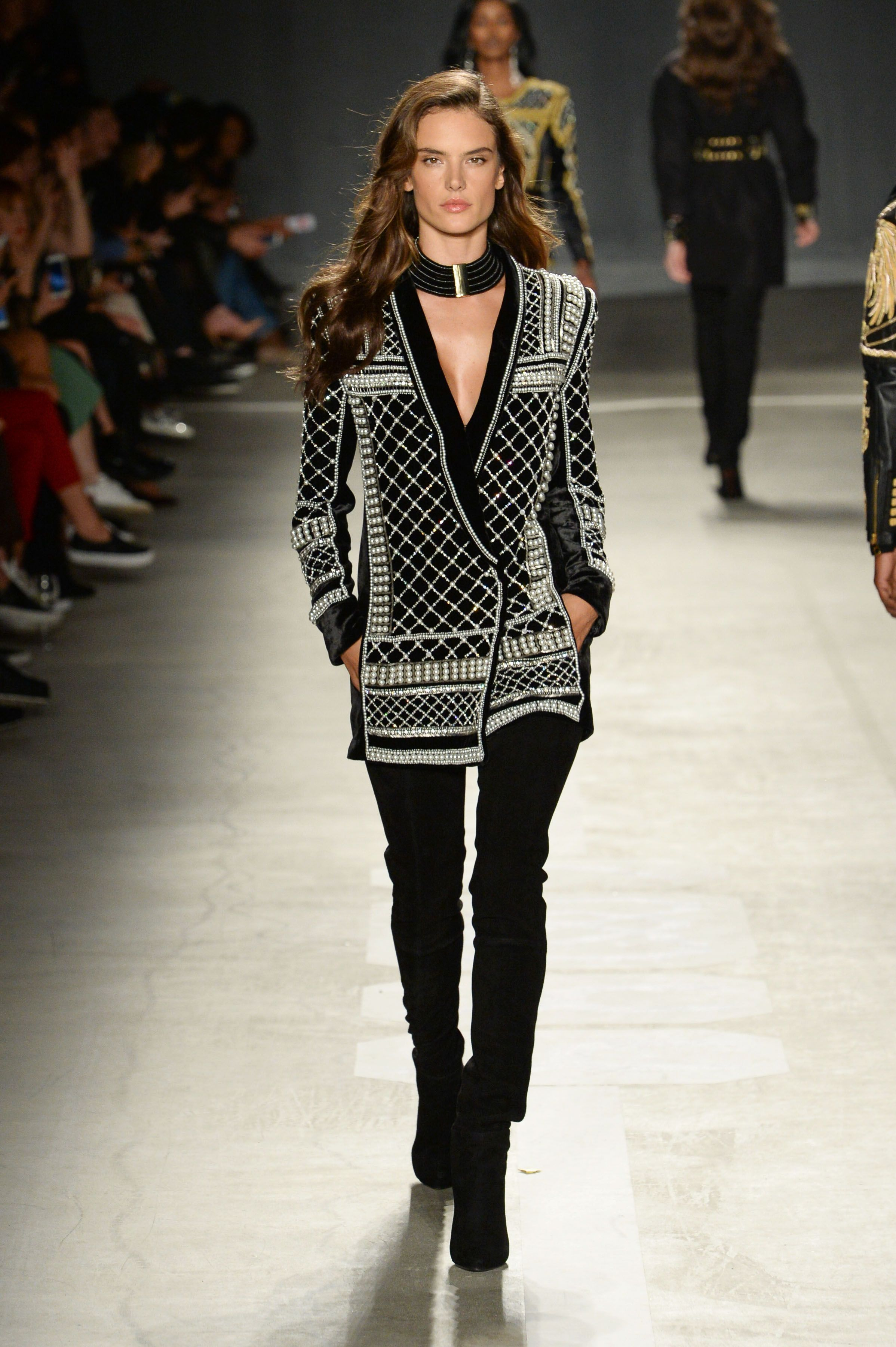 b70014fe Supermodel Alessandra Ambrosio dazzles the front row in a pearl embellished  blazer from the Balmain x H&M collection, available Nov. 5th.