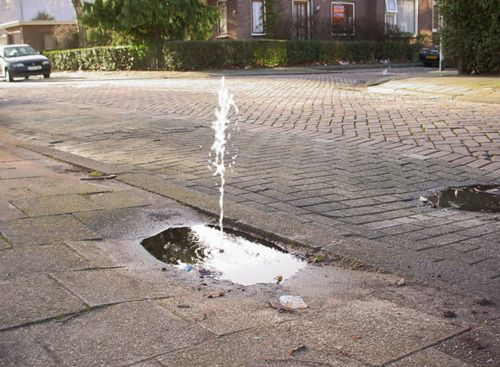 REFERENCEARTGALLERY:    Helmut Smits    Street Fountain 2002  Small water pumps in existing pot-holes in the road surface. When it rains, small fountains appear.