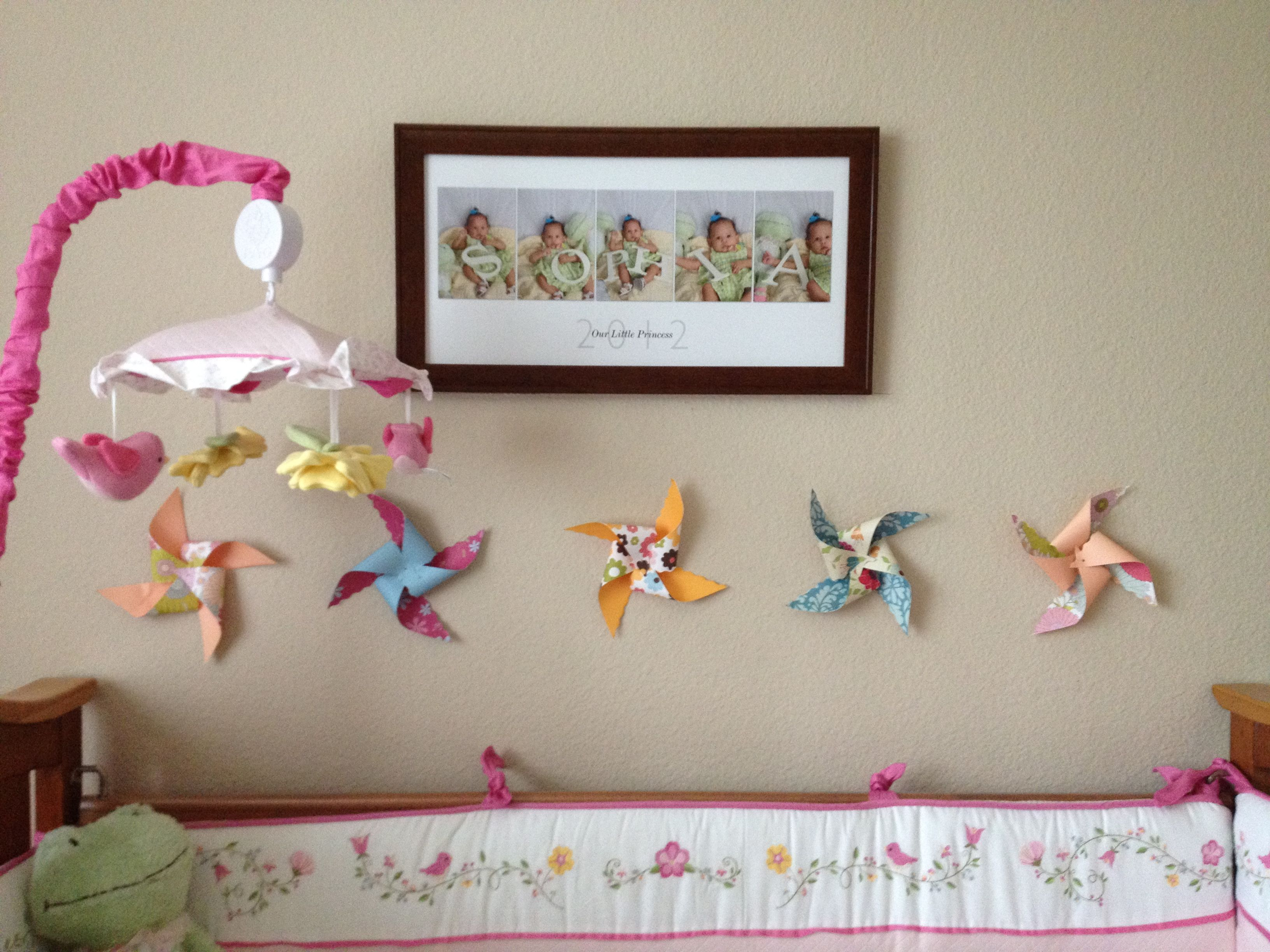 Sophie's wall. Pinwheels courtesy of my aunt Anne and uncle Tom's wedding, FAO Schwartz, bedding and mobile, and photo collage.