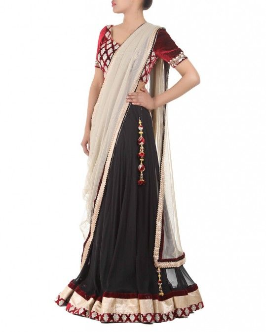 A Gorgeous Black & Maroon Lehenga featuring a Black Crepe Skirt complete with a three tier border made with Velvet, Lurex and Brocade and matching latkans on the waist fastening. The blouse is a short choli made with Maroon Velvet featuring brocade and a little beadwork along the sleeve bottom. The Gold Net Dupatta is an elegant contrast against the dark background colours, which features detailing on the border and beautiful latkans at the edges. #ootd #lehenga #indianwear #traditional