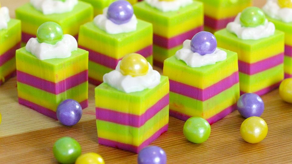 Recipe with video instructions: Colorful, boozy treats perfect for a festive Fat Tuesday. Ingredients: ¾ cup cold water, 3 tbsp powdered gelatin, ½ cup condensed milk, 1 cup raspberry-flavored vodka, 2 tbsp Irish crème liqueur, ½ cup + 2 tbsp water, purple, yellow and green food coloring, cooking spray, whipped cream, purple, yellow and green candies