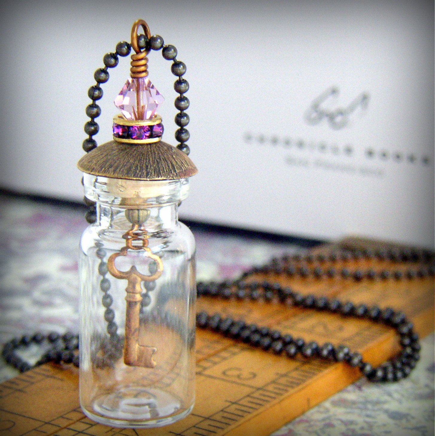 Glass Vial Necklace with Purple Crystal Bead and Dangling Key Charm. $20.00, via Etsy.