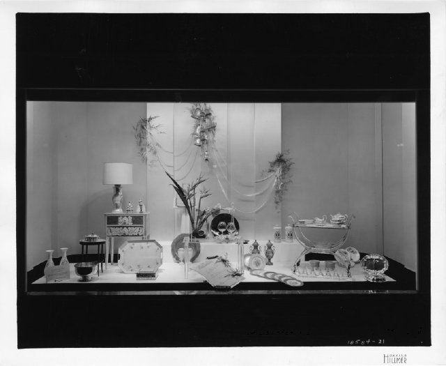"""The display features many differing types of home accessories including China, crystal, ornamental urns and vases, ceramic or porcelain figurines, end tables, and service ware for the table as well as guest entertainment. Signage in the central foreground reads, """"The Bride of Today, Will Treasure… Distinctive Wedding Gifts, Combine Beauty and Charm, Mezzanine, Woodward."""""""