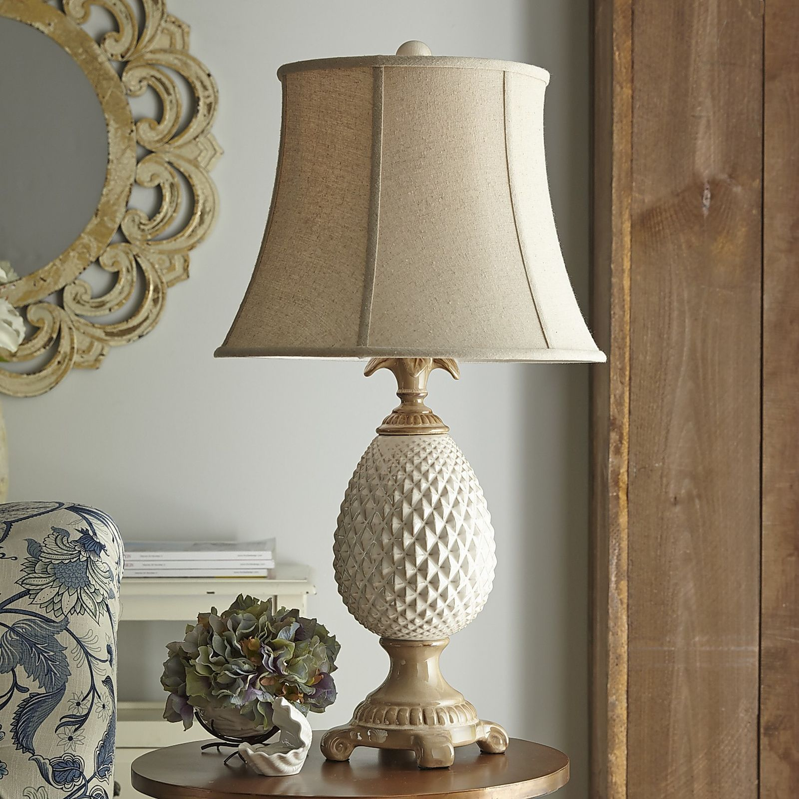 A symbol of hospitality since the 18th century, this pineapple lamp extends a serene welcome to guests. Equally at home in refined or casual decor, it's cast in shades of antiqued porcelain, stands square on four curled feet and is fitted with an unbleached linen shade and sprouting finial. Sweet.