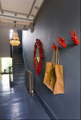 Vermilion has been on my mind since I picked up an African headress and thought it would look fabulous against a dark wall. Here Abigail Ahern does it with hooks and mirrors.