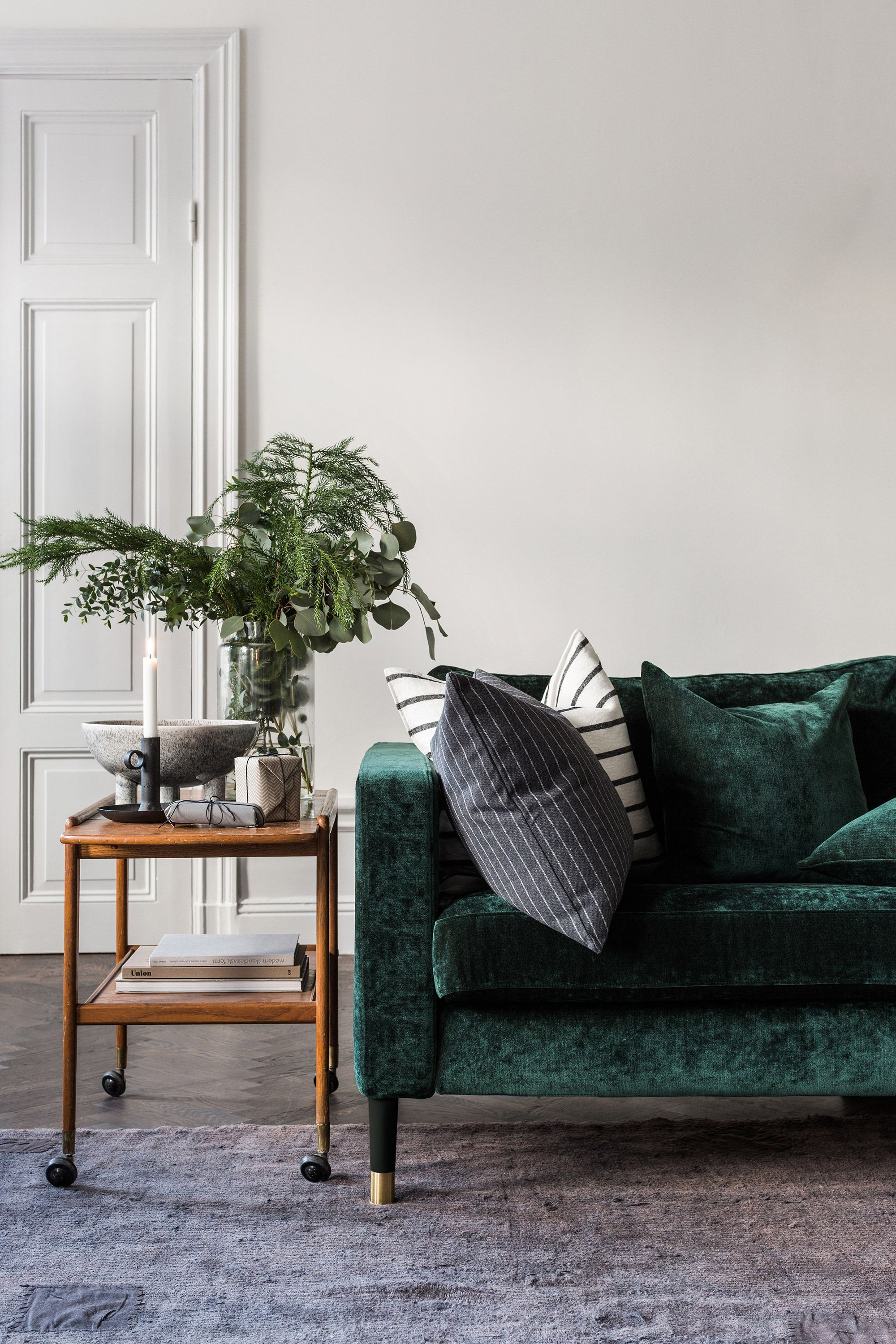 luxe green velvet sofa | retro bar cart sideboard | fir tree and eucalyptus bouquet | IKEA Karlstad sofa with a Bemz cover in Viridian velvet by Designers Guild | Bemz cushion covers | panelled wooden door | herringbone floors