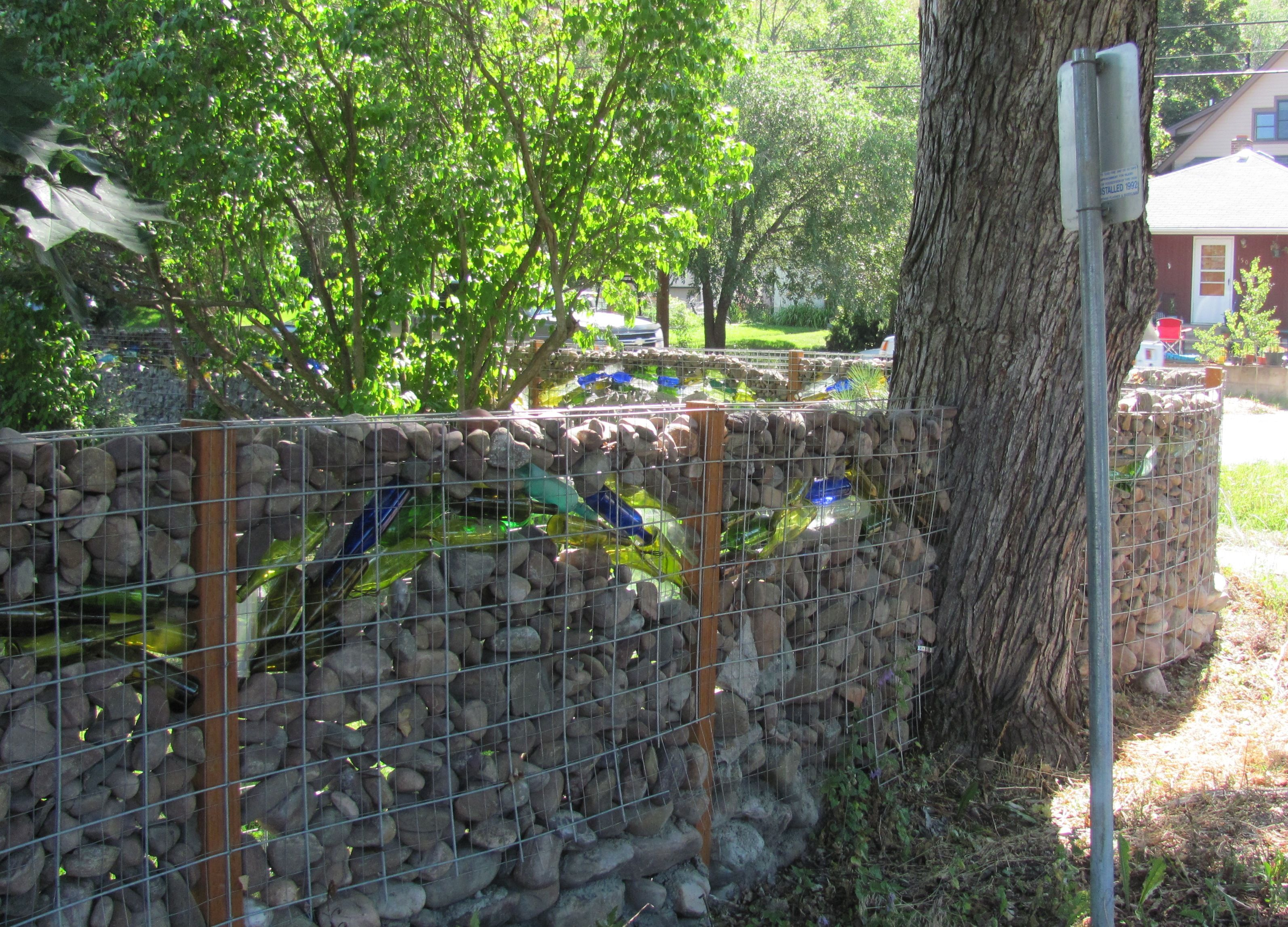 Glass bottle gabion - as fence...also sun shines through bottles and ...