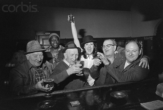 Woman posing with men in a bar in the Poletown neighborhood of Detroit. The neighborhood is being razed so a General Motors plant can be built.