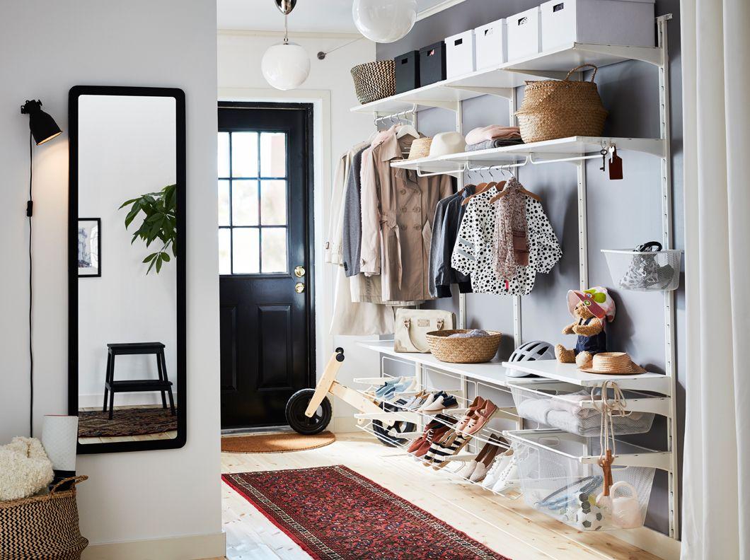 Stor entré med oppbevaring fra gulv til tak, bestående av hvite hyller, trådkurver, skohyller og stativer til oppbevaring av klær, vesker og sko.