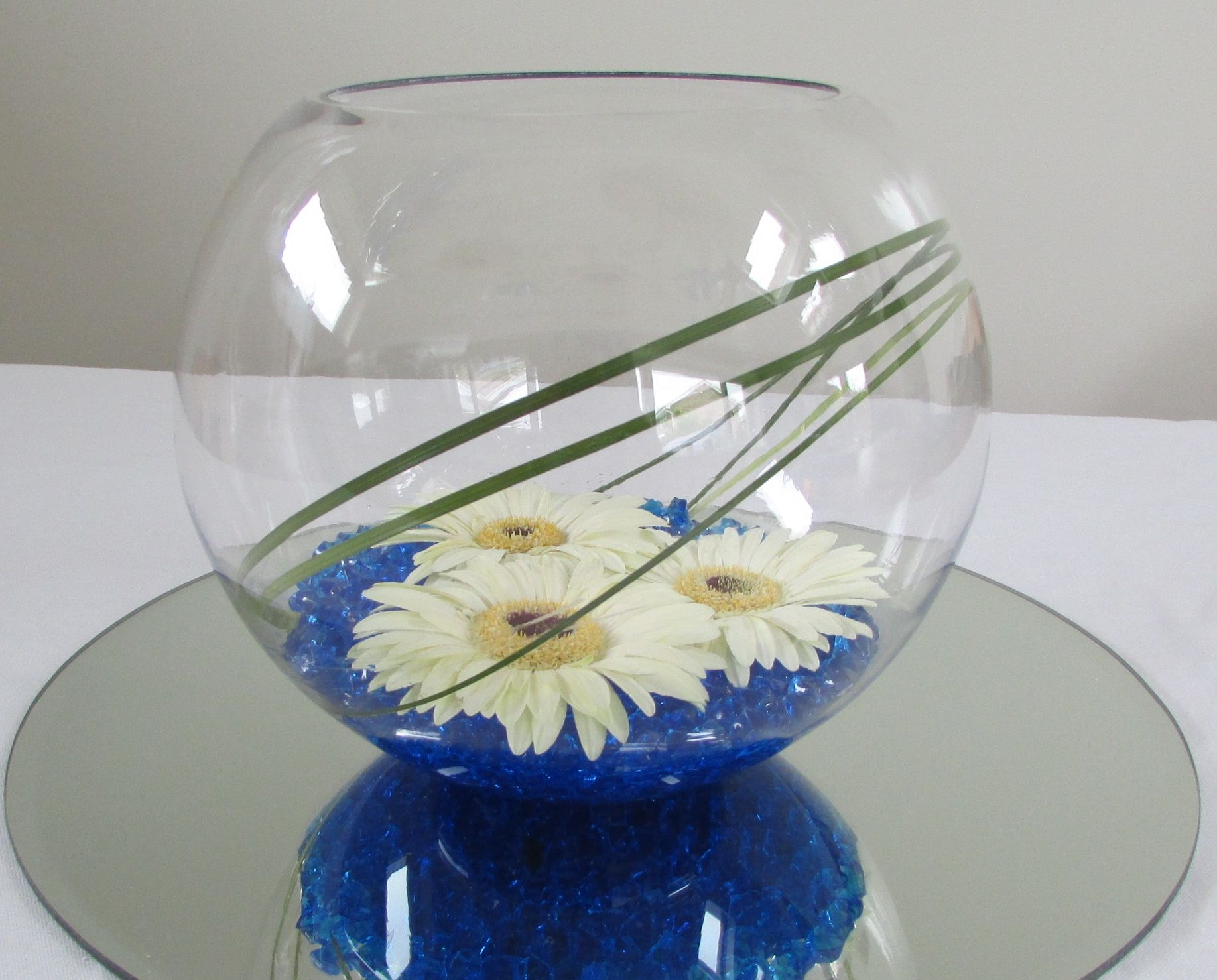Goldfish bowl with blue gems and white gerbera table