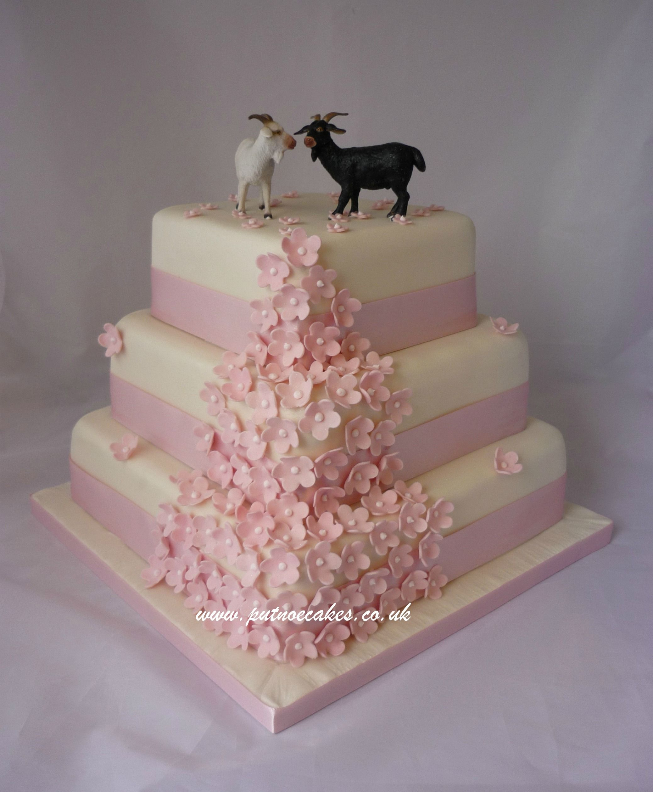 White wedding cake with pale pink blossoms, topper off by