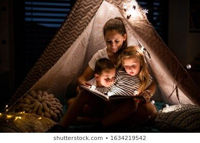 Mother with children sitting indoors in bedroom, reading a book. #beautiful, #bedroom, #bonding, #book, #boy, #caucasian, #cheerful, #childhood, #children, #comfort, #cosy, #dark, #daugther, #domestic, #evening, #family, #females, #flat, #girl, #happy, #harmony, #house, #indoors, #inside, #joy, #kids, #leisure, #lifestyle, #light, #lights, #love, #mother, #offline, #offspring, #peace, #reading, #relationship, #room, #sitting, #small, #son, #technology, #tent, #time, #together, #tranquillity, #us