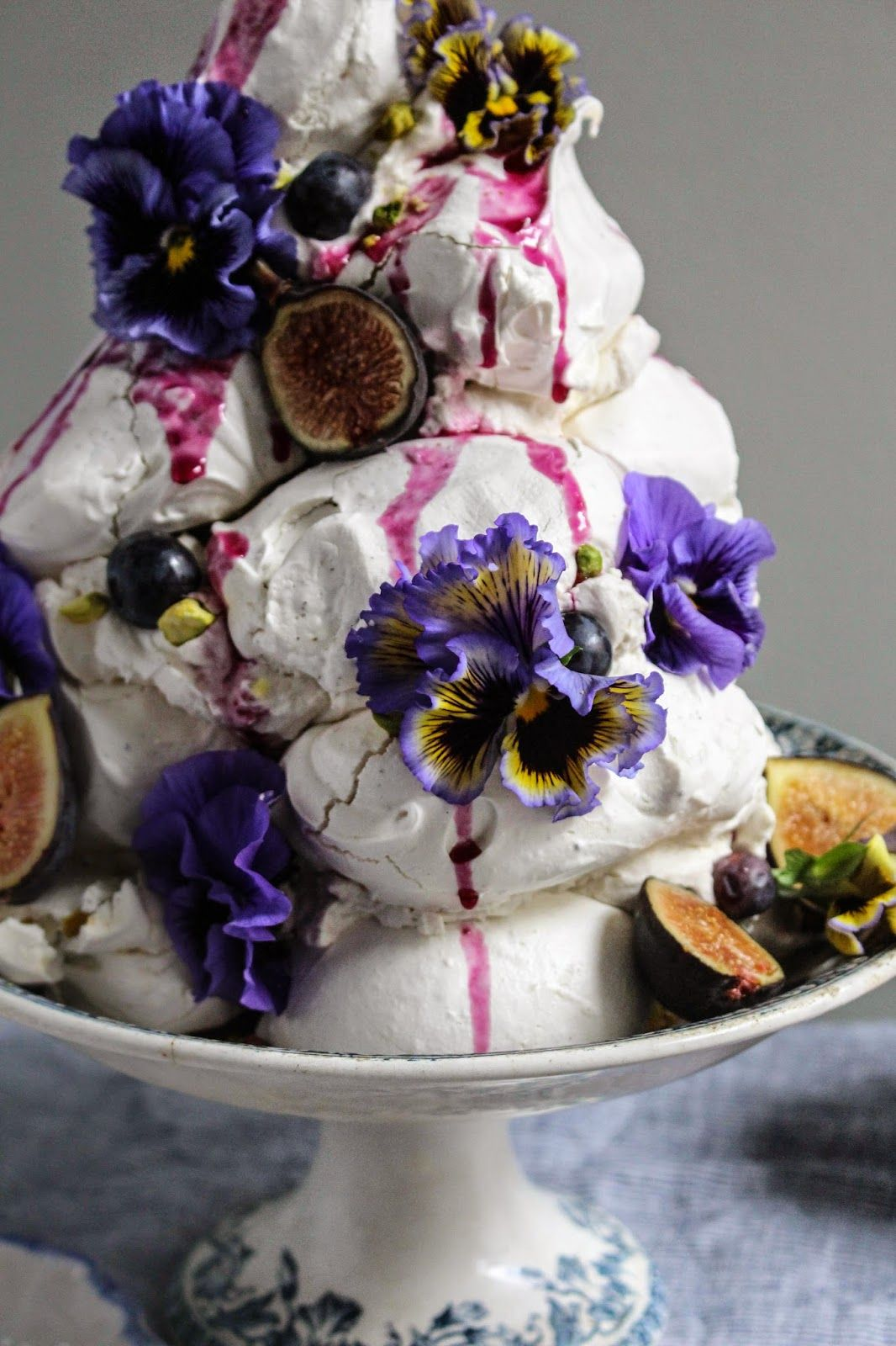 Photo of earl grey pistachio meringue tower with blueberries and figs and edible flowers