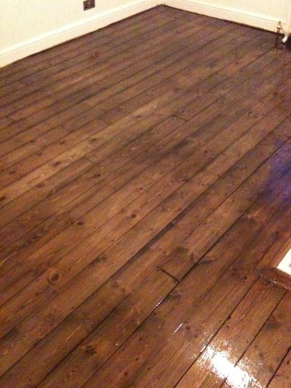 Pine floorboards after floor sanding, staining with dark