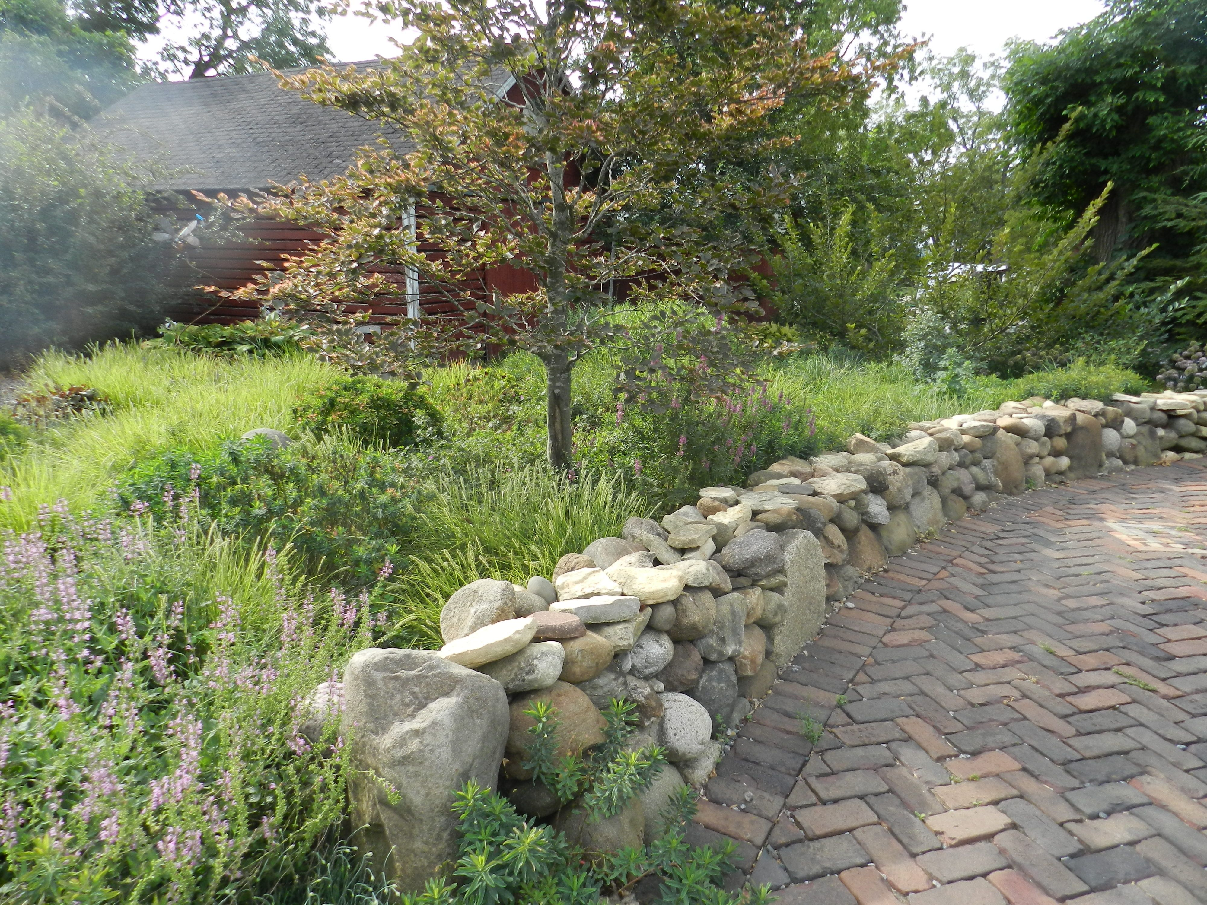 A dry-stacked stone wall and brick pathway create an entry way to ...