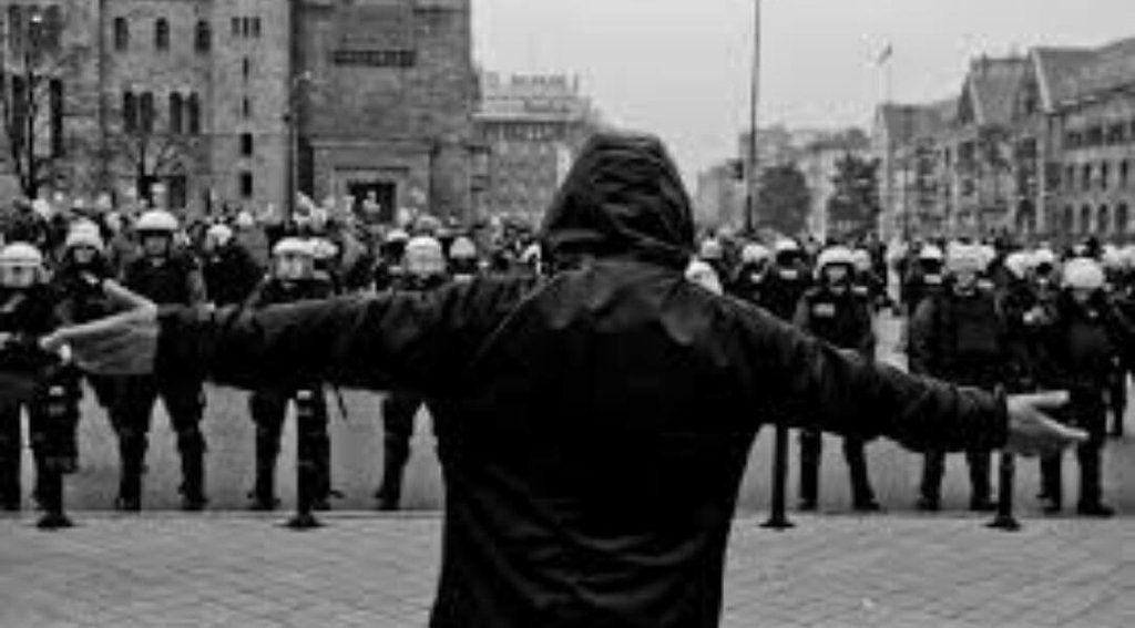 un teppista fotografato da vicino visto dalle spalle incita il cordone della polizia sullo sfondo