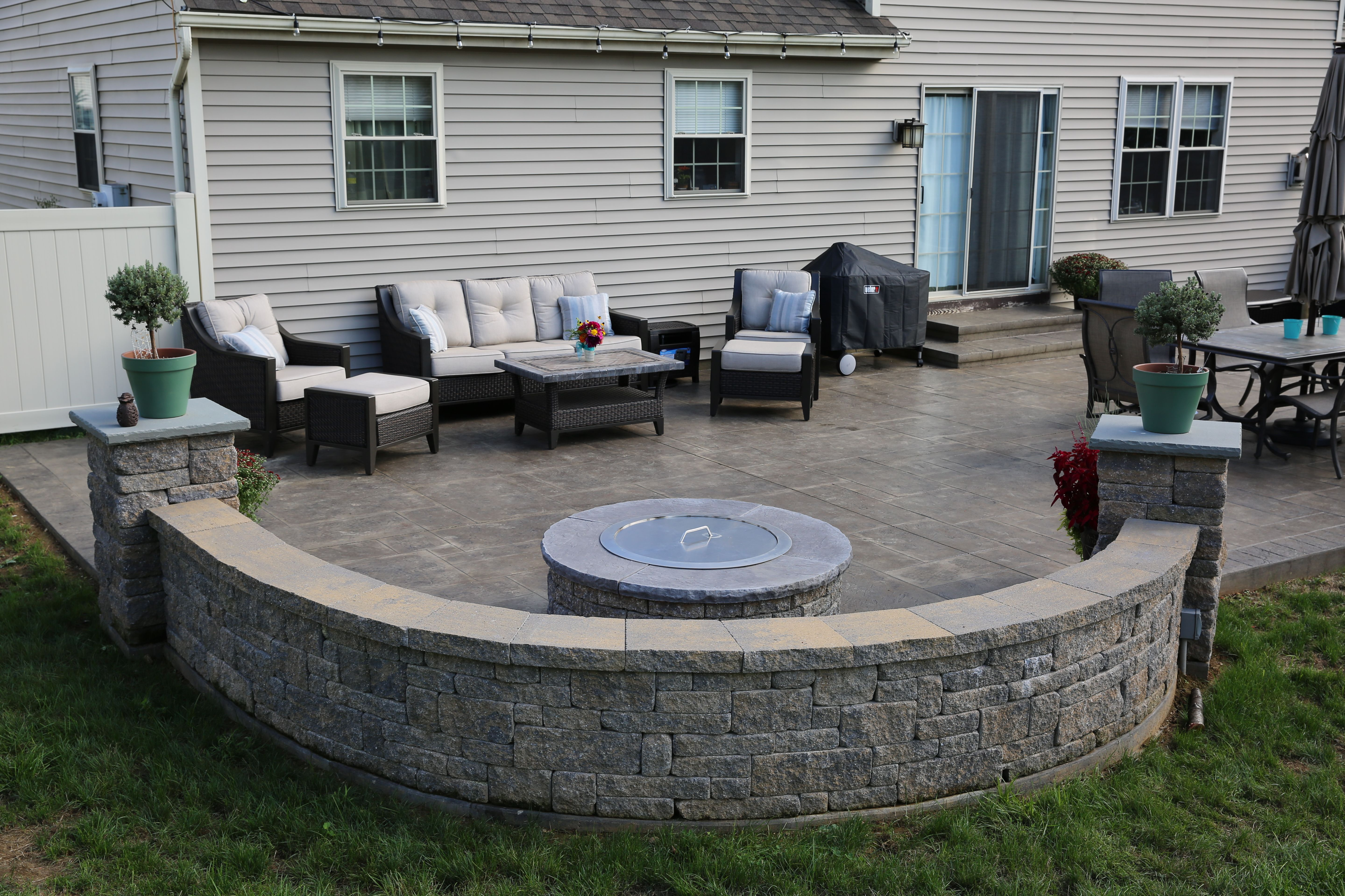 Paver Wall And Pillars Stamped Concrete Patio And Paver Fire Pit Concrete Backyard Concrete Patio Designs Patio Landscaping