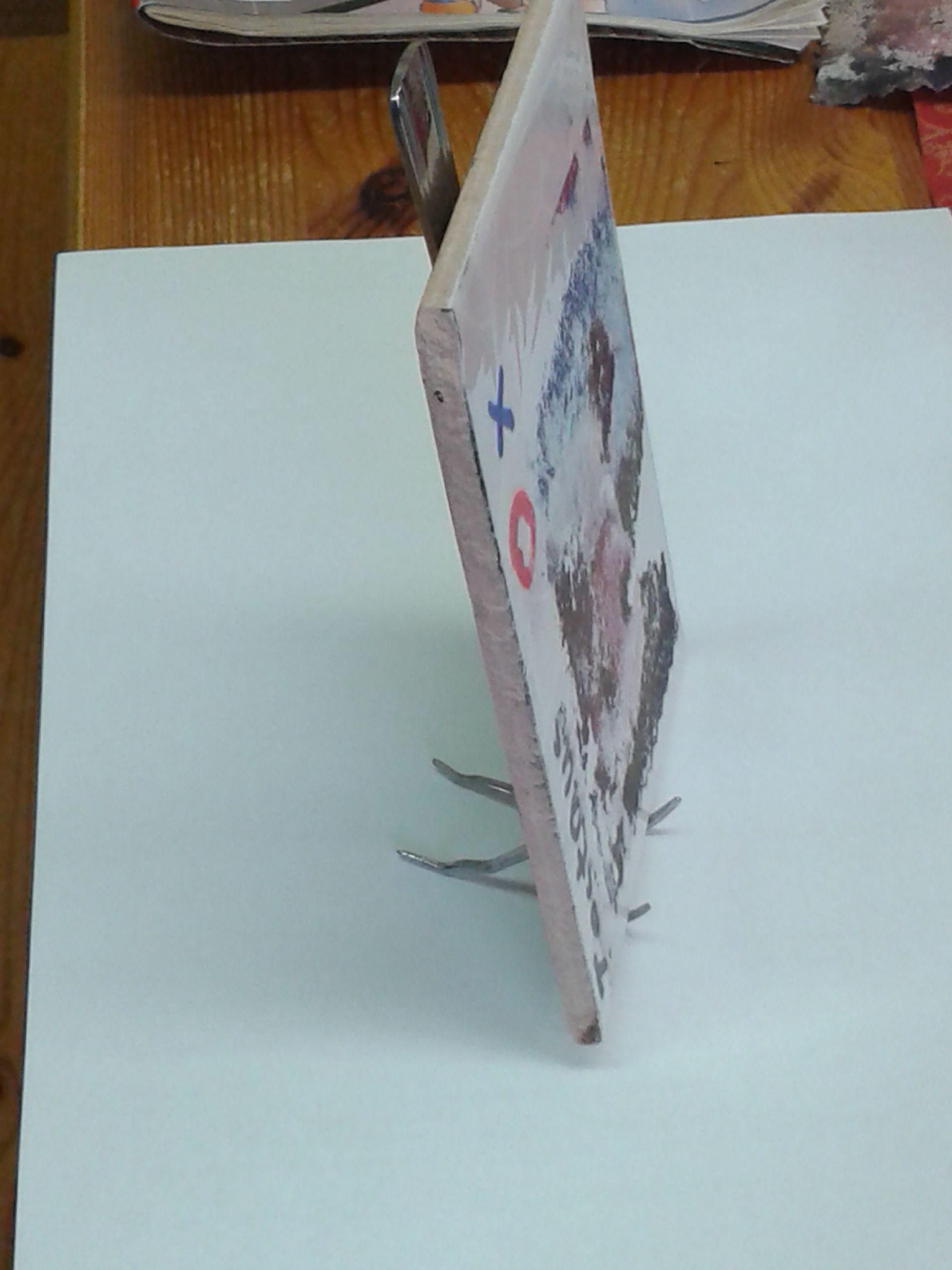 Tulosta kuva, laita se ylösalaisin kaakelille, kastele kynsilakanpoistoaineella kauttaaltaan, ota paperi varovasti pois, sivele lakkakerros päälle.     Pidikkeenä haarukka. Tässä toimii parhaiten nelipiikkinen, jossa mieluusti pitkät piikit. Käytä pihtejä piikkien taivuttamiseen, uloimmat piikit eteenpäin kaakelitaulua pitelemään ja sisemmät taaksepäin tueksi.