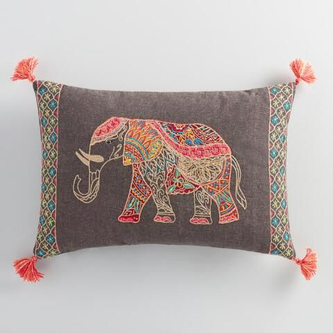 We're smitten with this exquisite taupe lumbar pillow featuring an embroidered elephant embellished with patches of vibrant-patterned fabric in warm hues and hints of shiny gold thread.