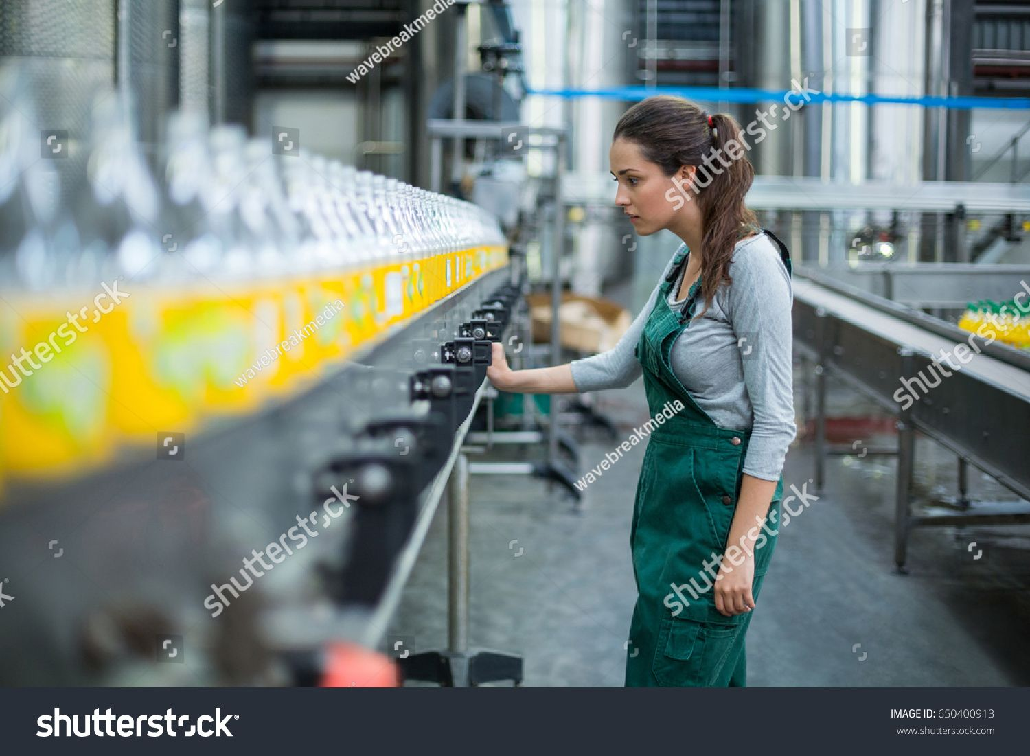 Female factory worker inspecting production line at drinks