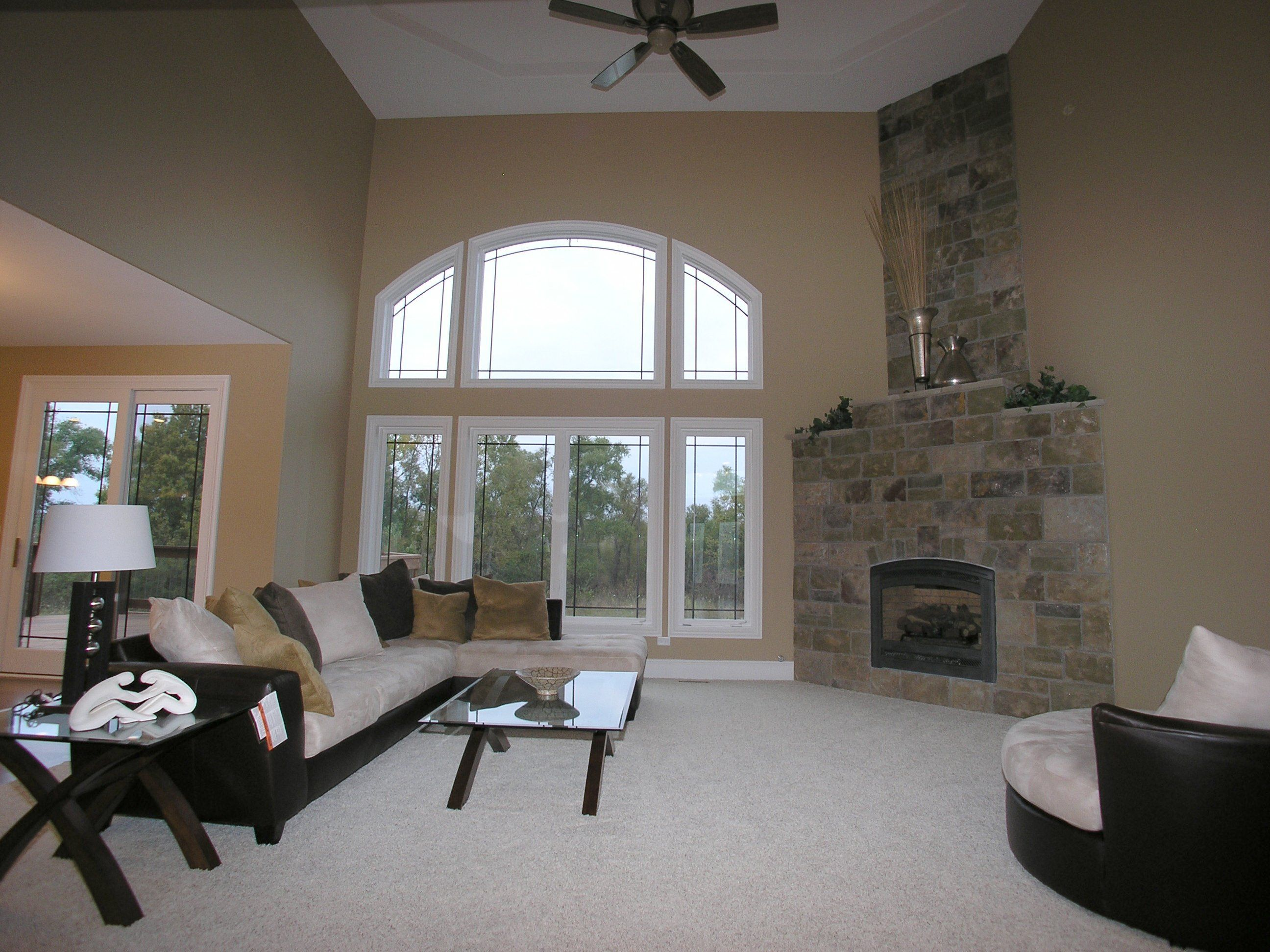 Living Room With High Ceilings Large Windows And Corner Fireplace